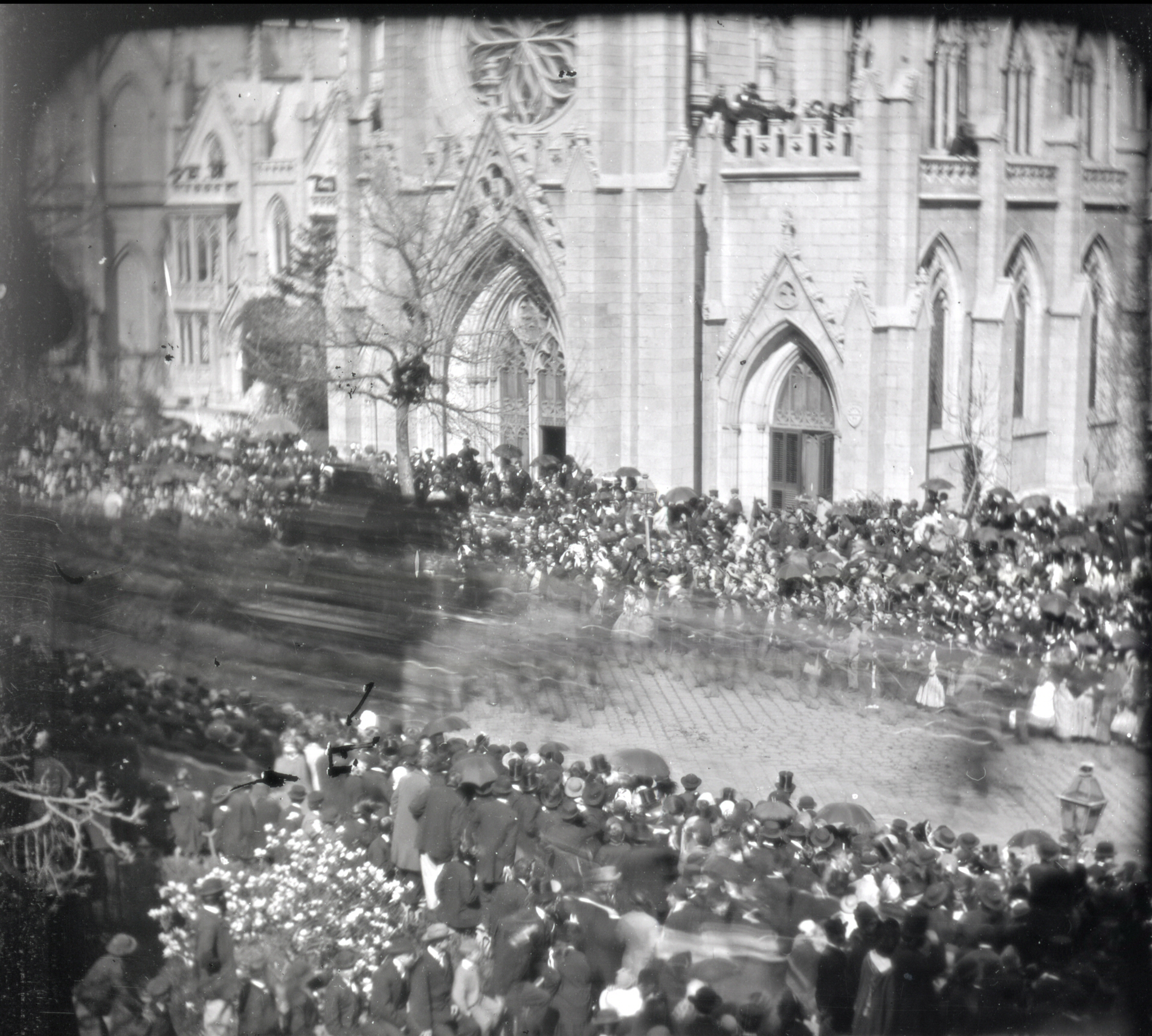 Second image (again, click to super-size). A procession passes. What is the dark blurred object at the left?
